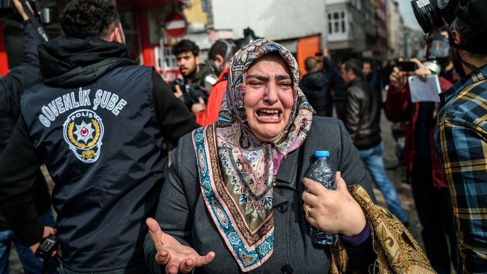 A woman cries as Turkish anti-riot police officers disperse supporters in front of the headquarters of the Turkish daily newspaper Zaman in Istanbul on March 5, 2016, after Turkish authorities seized the headquarters in a midnight raid.
