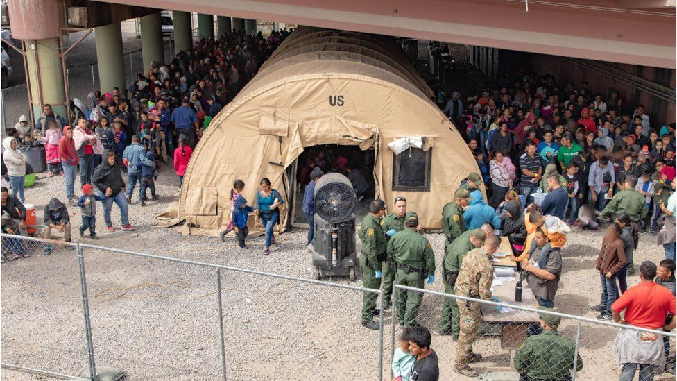 Border Patrol agents, including members of U.S. Border Patrol's BORSTAR teams (in tactical uniforms) provide food, water and medical screening to scores of migrants at a processing centre