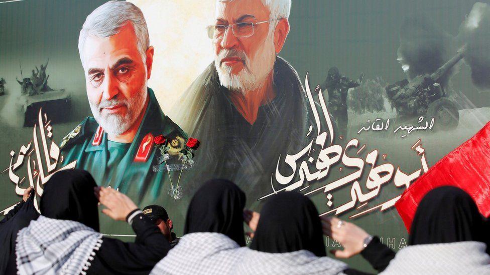 Iraqi women salute a poster of Qasem Soleimani (L) and Abu Mahdi al-Muhandis near where the two men were killed in a US drone strike in Baghdad(29 June 2020)