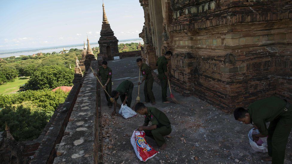 Myanmar military staff collect pieces of bricks at the damaged ancient Htilominlo Temple on 25 August 2016.