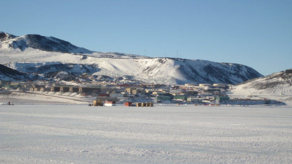 A collection of buildings at the base of a slope, dusted in snow