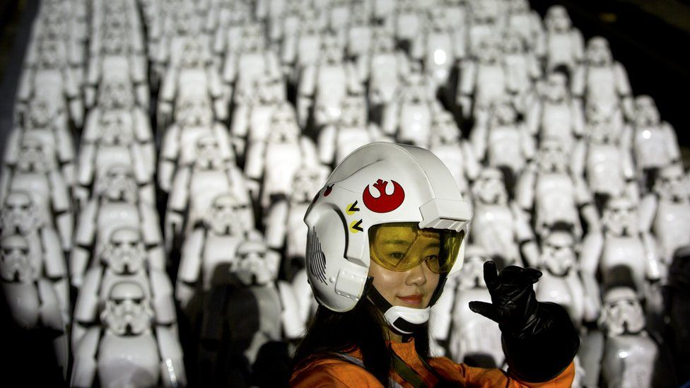 A Chinese fan poses for a photo in front of storm troopers at the Great Wall of China