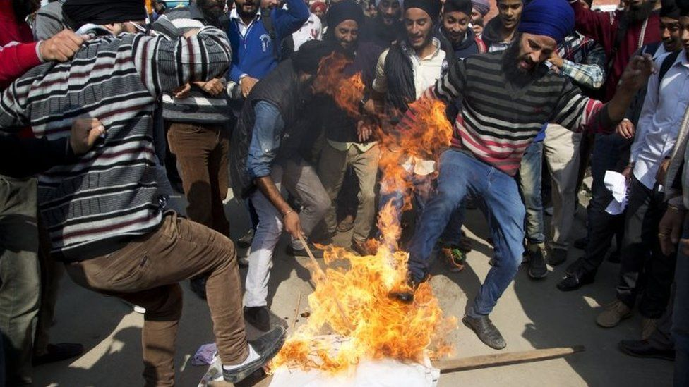 Kashmiri Sikhs kick a burning effigy of Gurmeet Ram Rahim Singh, chief of a religious sect Dera Sacha Sauda, during a protest against the killing of two Sikh boys, in Srinagar, Indian controlled Kashmir, Saturday, Oct. 17, 2015