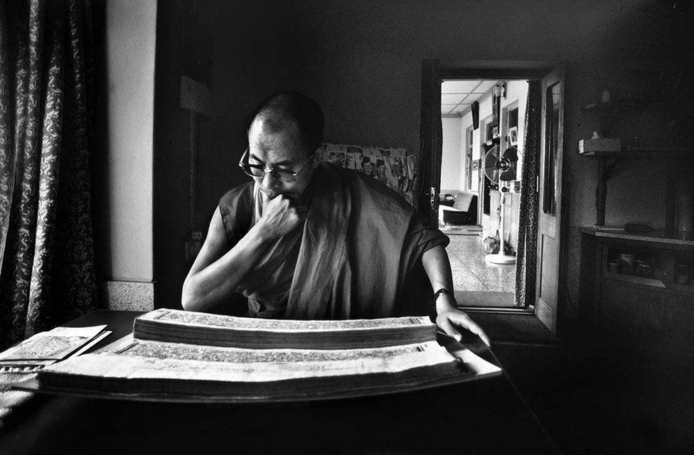 The Dalai Lama reading Tibetan scriptures