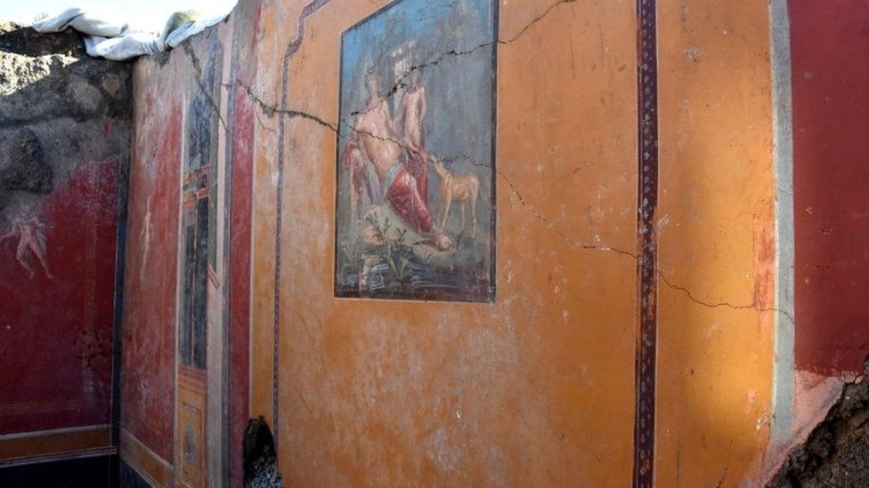 Wider shot of the room with the fresco in frame
