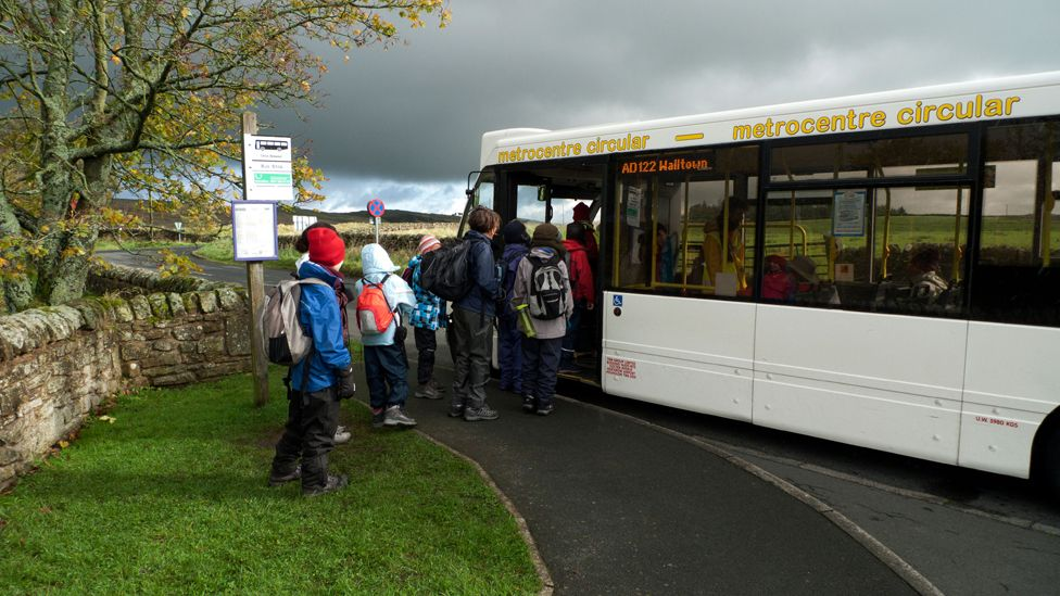 Schoolchildren tour group boarding a bus at Once Brewed near Hadrian's Wall, Northumberland, England