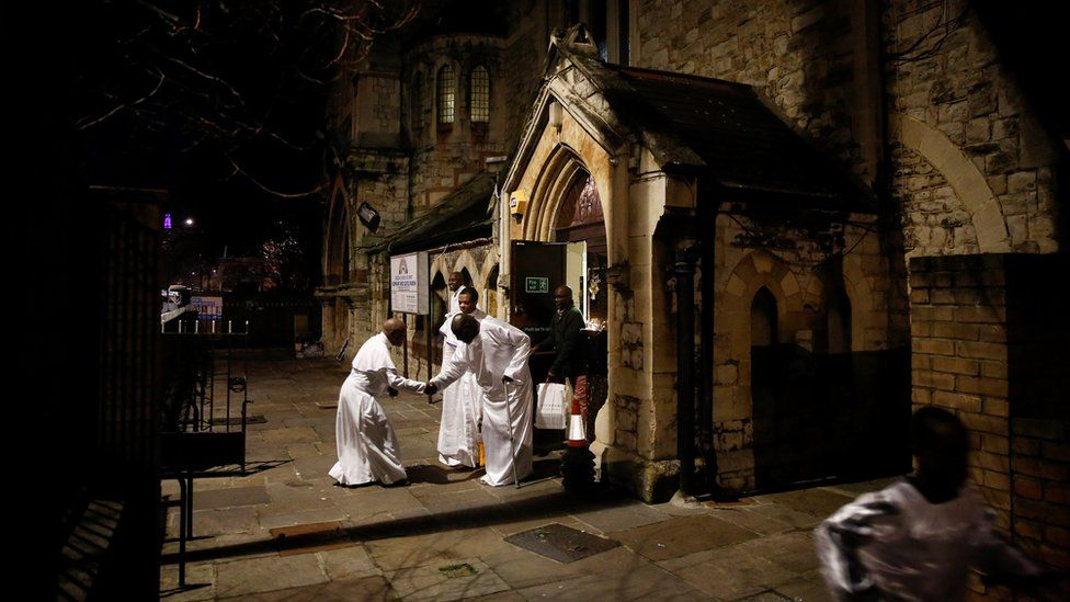 Worshippers greet following a night-time Christmas Eve service at the Celestial Church of Christ in Elephant and Castle