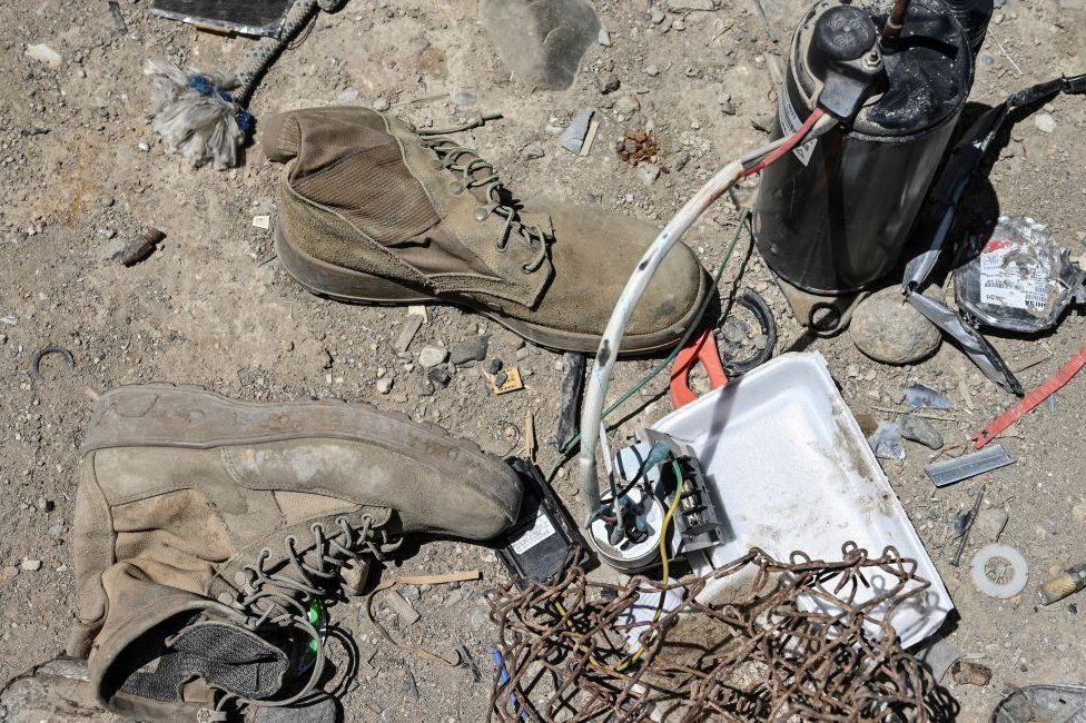 A pair of military boots lie on the floor next to other abandoned equipment in a scrap yard near Bagram airbase.