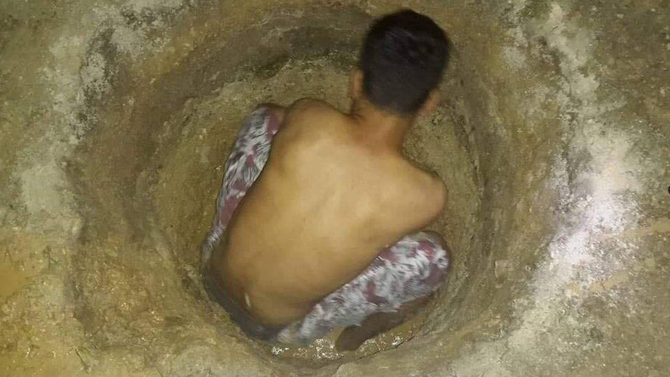 A detainee on Manus Island digging a hole in the ground to find water