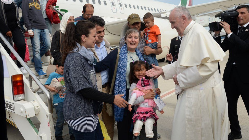Pope Francis welcomes a group of Syrian refugees after landing at Ciampino airport in Rome following a visit at the Moria refugee camp on April 16, 2016 in the Greek island of Lesbos. Twelve Syrian refugees were accompanying Pope Francis on his return flight to Rome after his visit to Lesbos on Saturday and will be housed in the Vatican, the Holy See said.