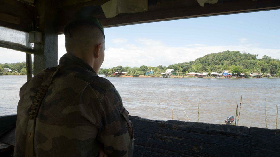 A legionnaire on look-out duty looks out from French Guiana towards Brazil