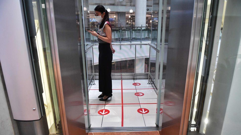 A woman stands in an elevator with markers on the floor for social distancing measures in a shopping mall amid concerns over the spread of the COVID-19 coronavirus in Bangkok on March 20, 2020