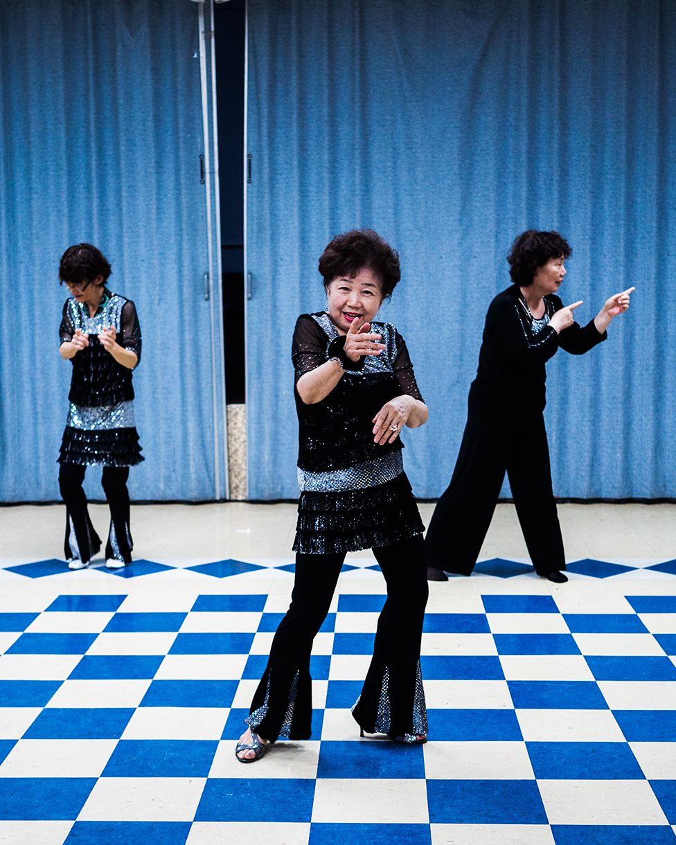Three women dance and pose for the camera