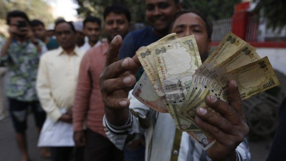 An Indian man displays Indian currency notes of 1000 and 500 rupees as he stands in queue to exchange or deposit discontinued currency notes outside a post office in Ahmadabad, India, Thursday, Nov. 10, 2016