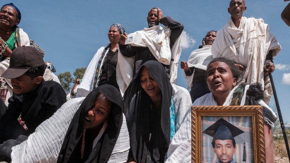 Les gens réagissent alors qu'ils se tiennent à côté d'une fosse commune contenant les corps de 81 victimes des forces érythréennes et éthiopiennes, tuées lors des violences des mois précédents, dans la ville de Wukro, au nord de Mekele, le 28 février 2021.