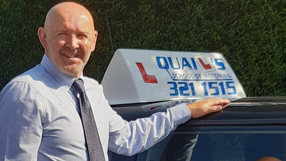 Graham Quail next to one of Quail's School of Motoring's vehicles