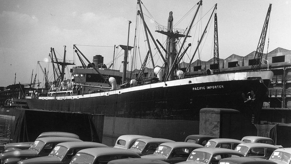 1948: SS Pacific Importer in the Manchester Ship Canal. Cars waiting for transport line the quay.