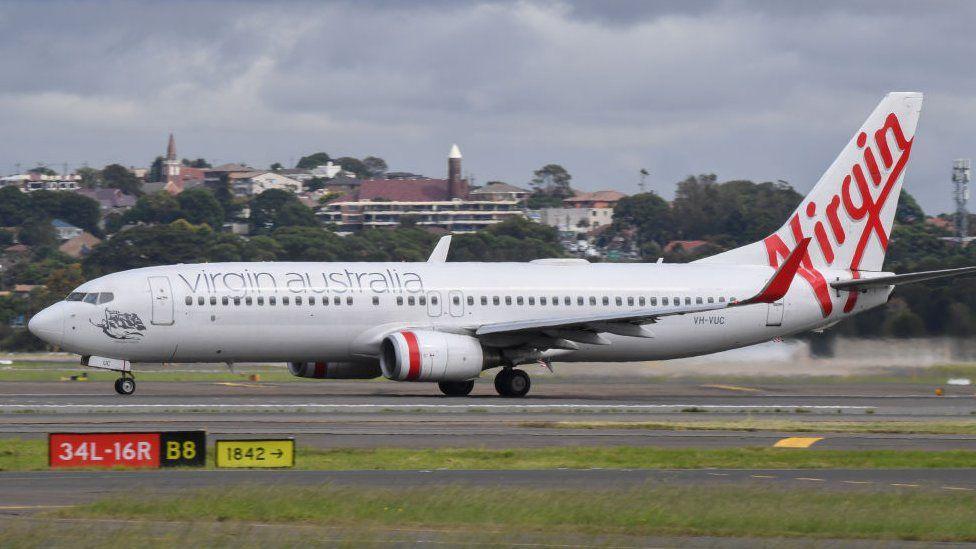 A Virgin Australia Boeing 737-800 series aircraft on the runway at Sydney's main international airport.