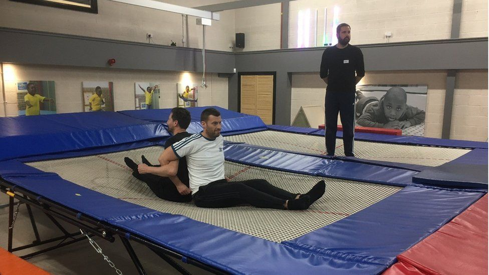 Two men sitting on the trampoline back-to-back
