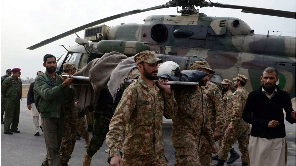 Pakistani soldiers walking with a stretcher in front of a helicopter carry an injured victim of a bomb blast in Parachinar, Peshawar, Pakistan, on 21 January 2017.