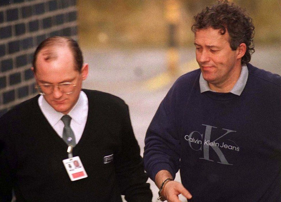 Barry Bennell, handcuffed to a custody officer, in 1998