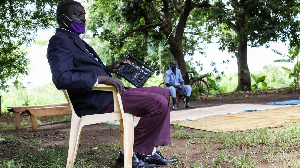 A man sitting on a chair outside and holding a radio in Lukodi, Uganda - Thursday 6 May 2021