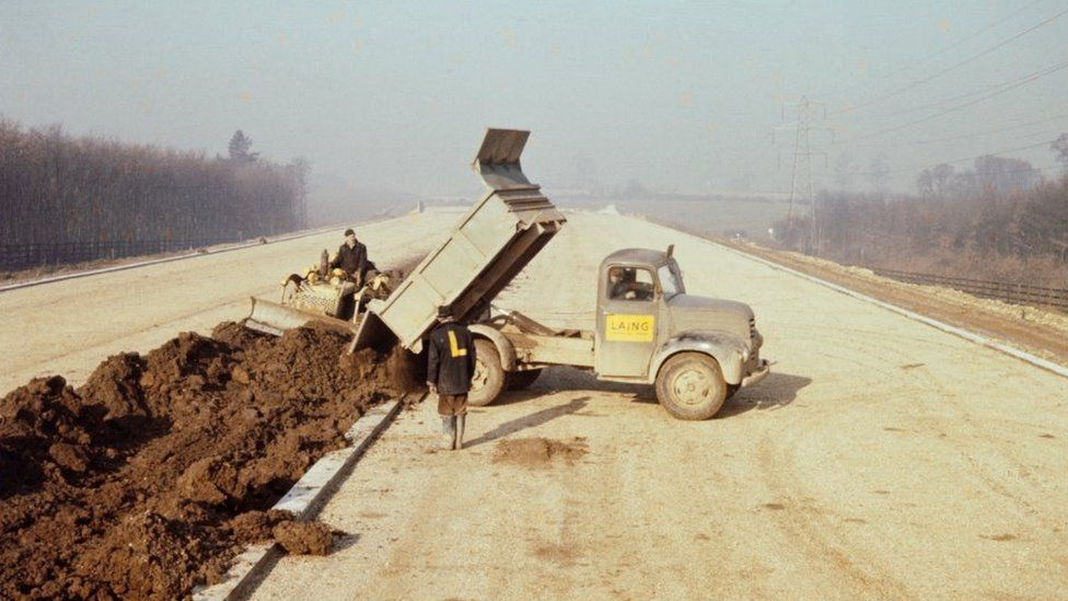 A lorry dumps soil for the central reservation