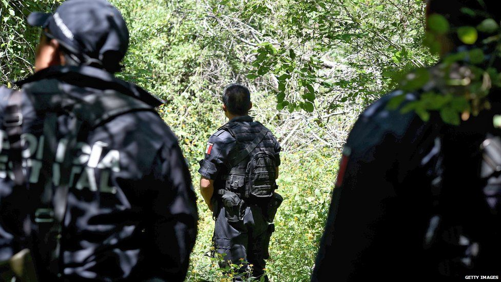 Police guard a mass grave outside Iguala. 9 Oct 2014