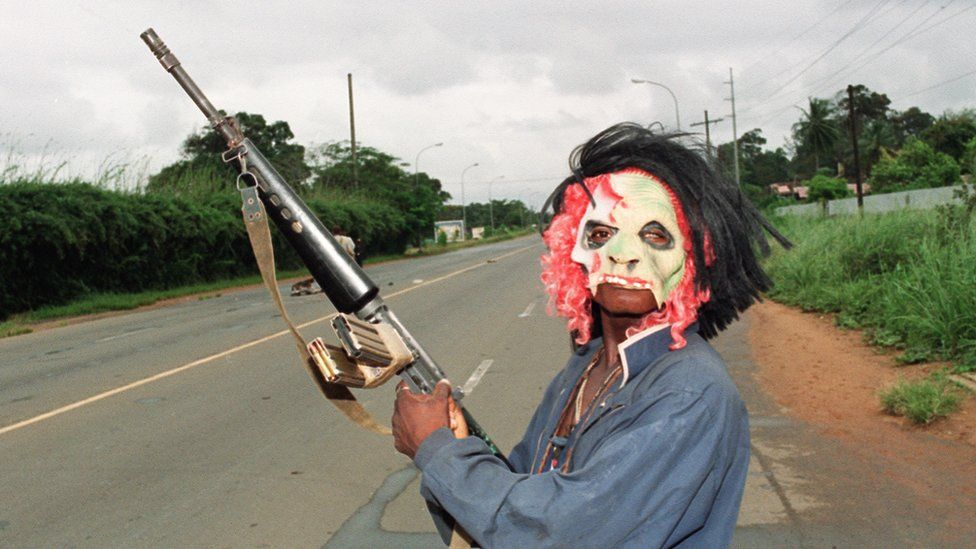 A masked rebel loyal to warlord Charles Taylor of the National Patriotic Front of Liberia (NPFL) holding a machine-gun patrol in the streets of Monrovia 11 August 1990