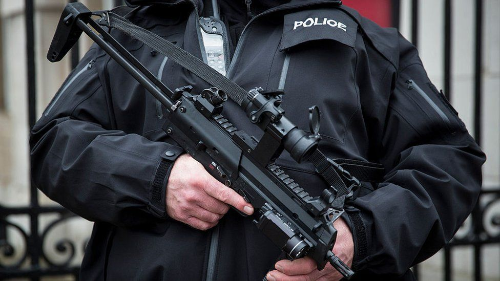 An armed police officer patrols on Whitehall