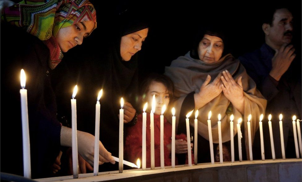 Pakistani women light candles during a vigil for victims of the Bacha Khan University attack, Wednesday, Jan. 20, 2016 in Peshawar, Pakistan