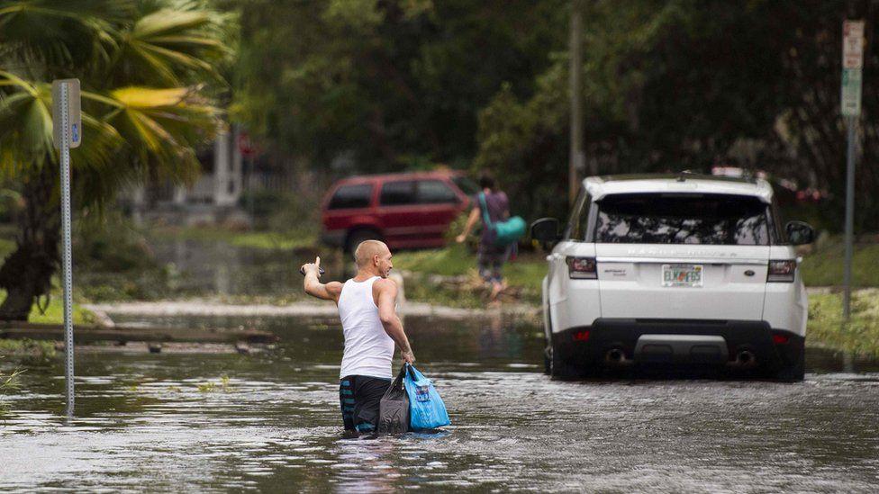 Man wades through flooded street in Florida