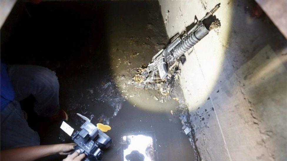 "A cameraman films next to a weapon found in a drain from where Joaquin ""El Chapo"" Guzman escaped"