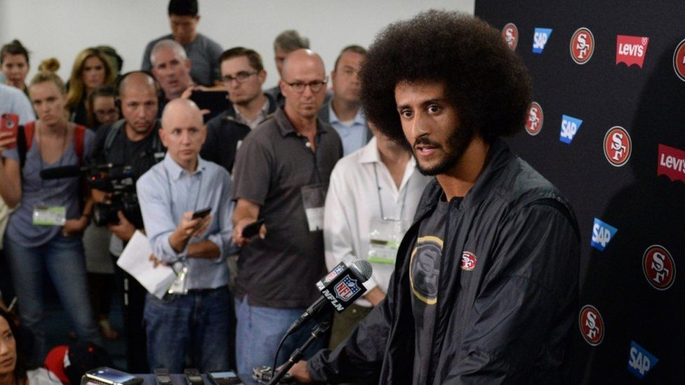 San Francisco 49ers quarterback Colin Kaepernick (right) talks to media after the game against the San Diego Chargers at Qualcomm Stadium