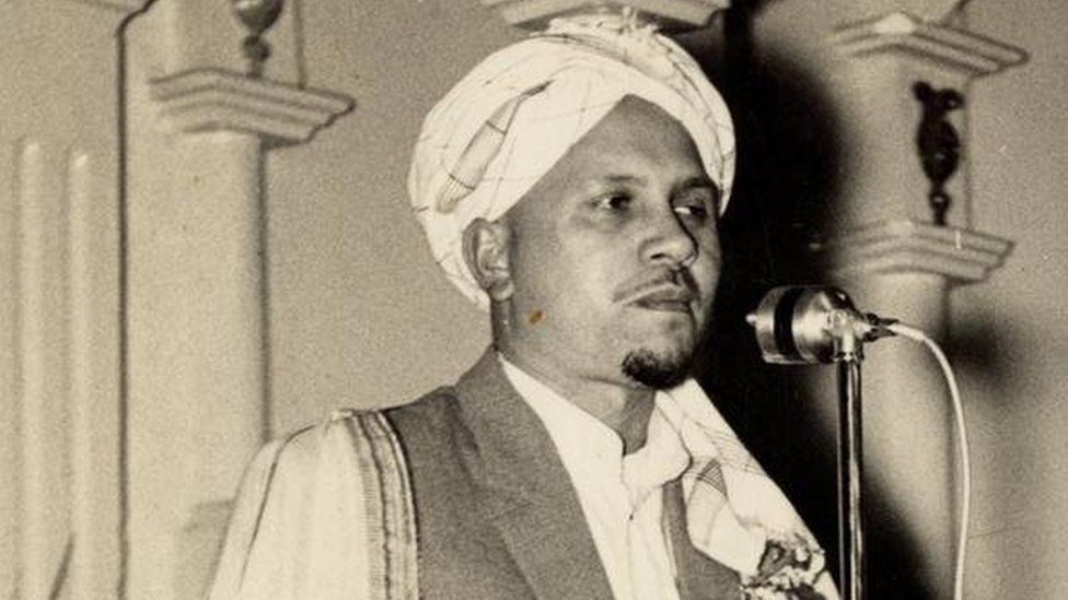 A black-and-white portrait of Imam Haron speaking to an audience with a microphone