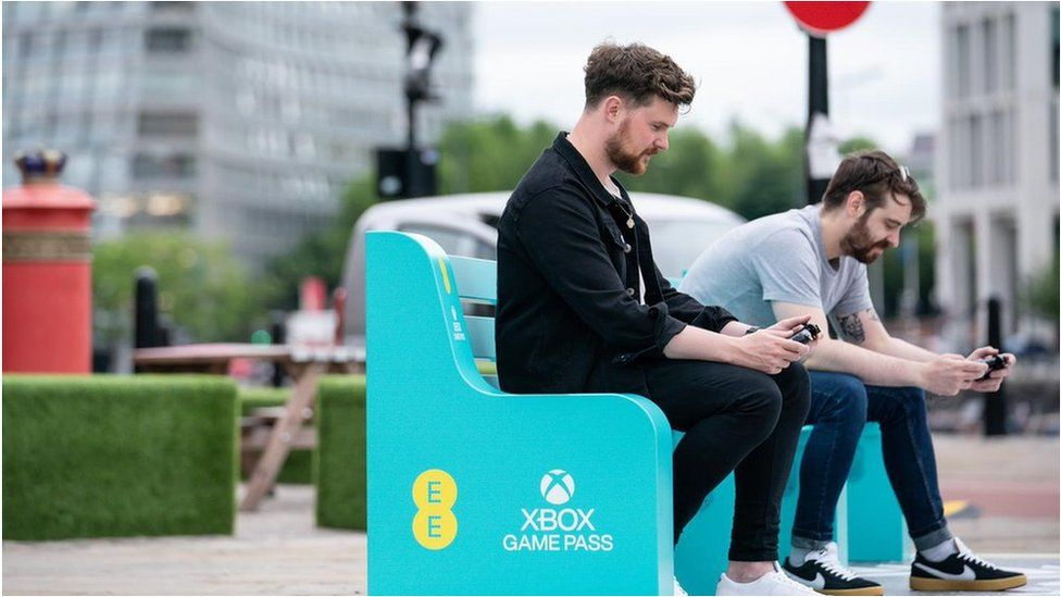 Phone users on an EE bench