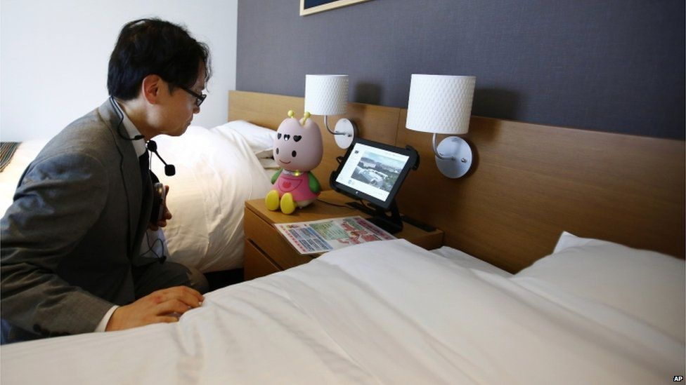 A hotel employee talks to concierge robot Tuly at the new robot hotel, aptly called Henn na Hotel or Weird Hotel, in Sasebo, southwestern Japan, Wednesday, 15 July 2015.