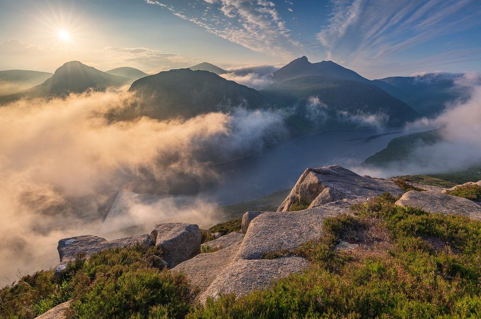 Sunrise over Ben Crom reservoir and peaks in the Mourne mountains in County Down as seen from the top of Slieve Binnian