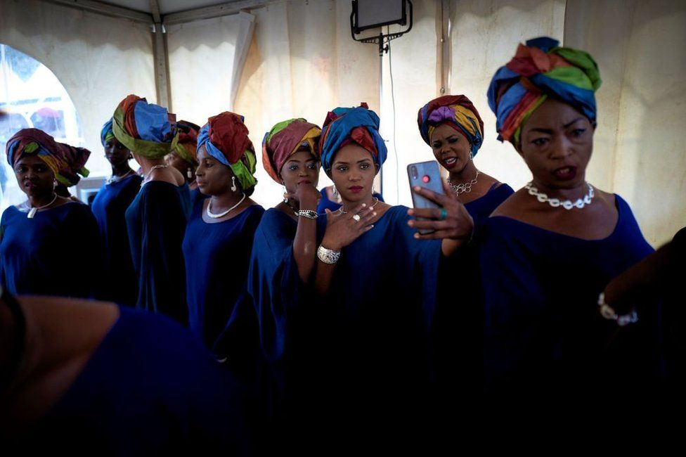 Women stand in line wearing jewellery, blue dresses and multicoloured headwraps in Mali - Friday 12 February 2021