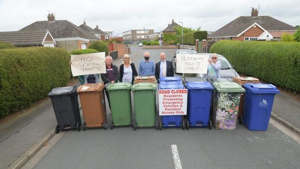 People lined up on a street with wheelie bins