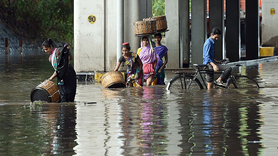 Indian pedestrians and a cyclist wade through a flooded street after heavy monsoon rain showers in Mumbai on June 21, 2016