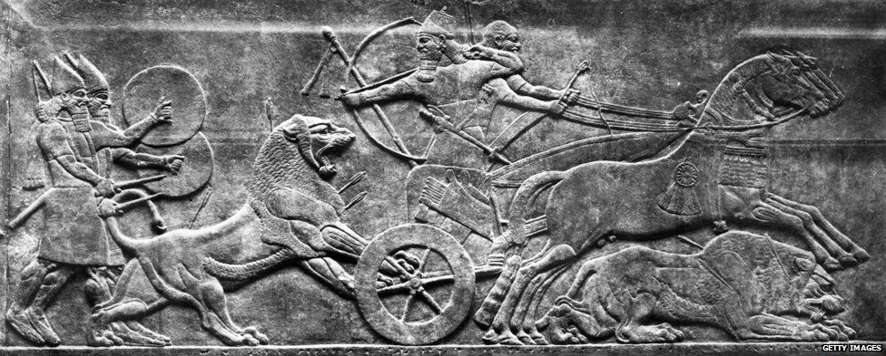 Circa 700 BC, Assyrians in a chariot, armed with bows and arrows, taking part in a lion hunt, on a frieze.