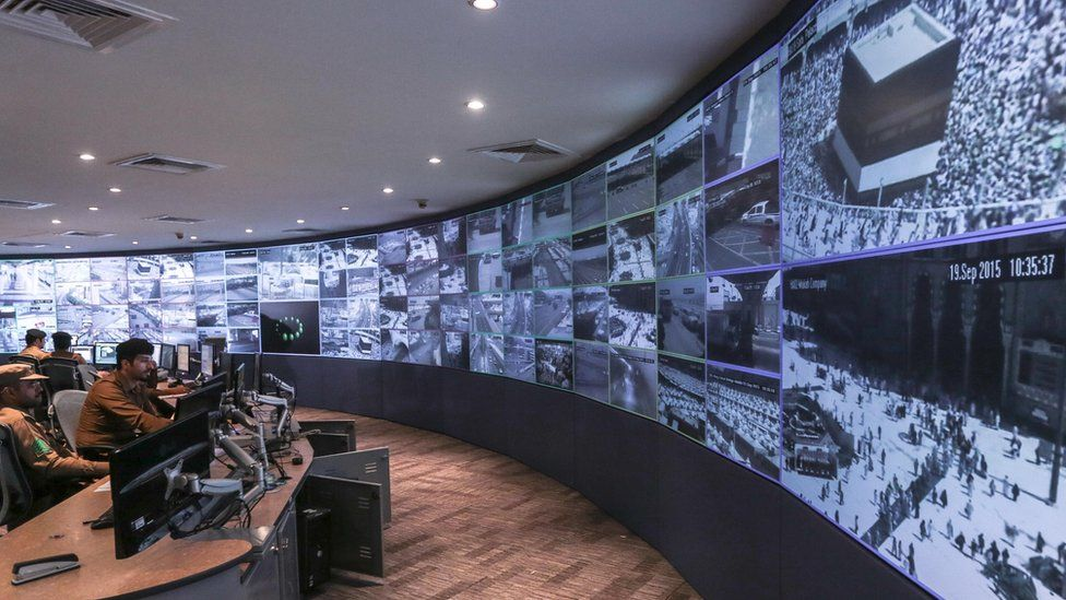 In this Saturday, Sept. 19, 2015 photo, Saudi security officers monitor live feed screens showing Muslim pilgrims in the holy city of Mecca, along with highways and high density areas, a few days before the annual pilgrimage, known as the hajj, in Mecca, Saudi Arabia