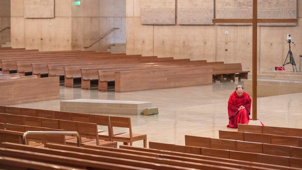 Father Brian Nunez kneels before a cross during Good Friday liturgy in an empty Cathedral of Our Lady of the Angels