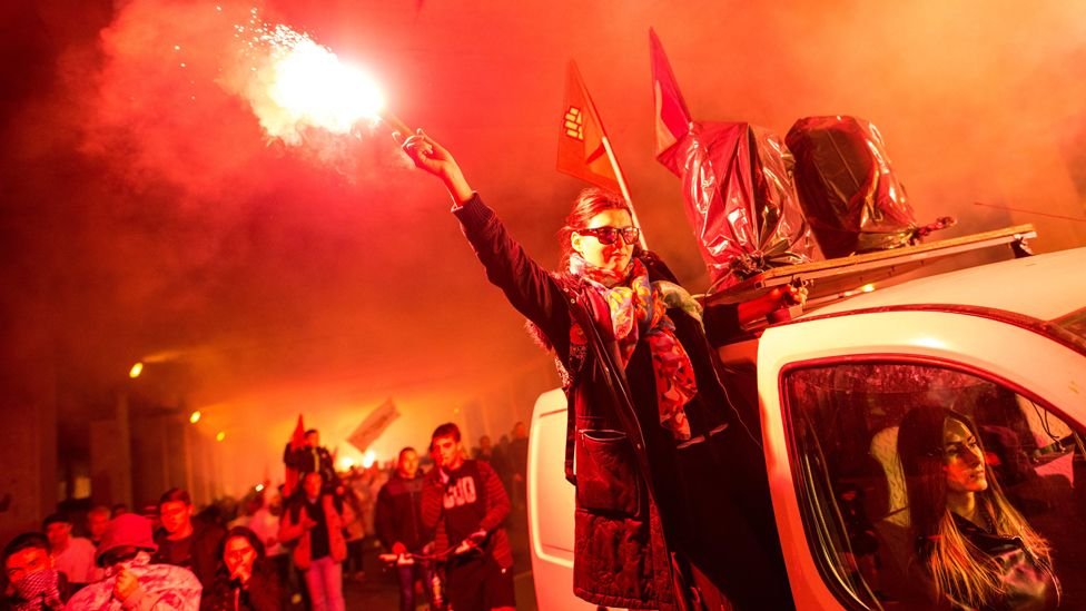 Protester holds flare in anti-government demo