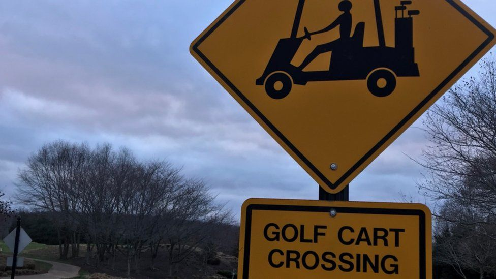 A road sign that marks a place for golf carts to cross