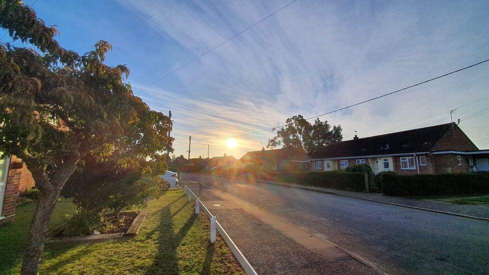 Sun rises over houses in Harleston