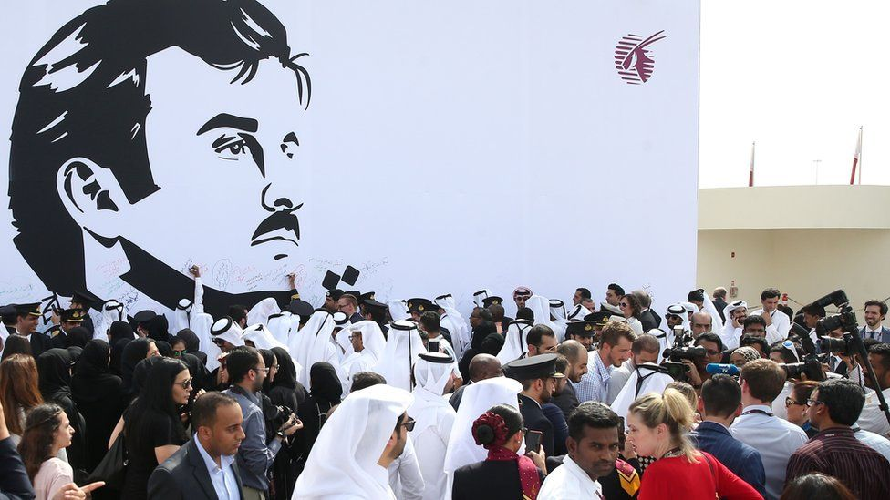 Qatar Airways workers stand in front of a wall bearing a portrait of Qatari Emir Sheikh Tamim bin Hamad Al Thani in support of the country and its leader in Doha. 13 July 2017