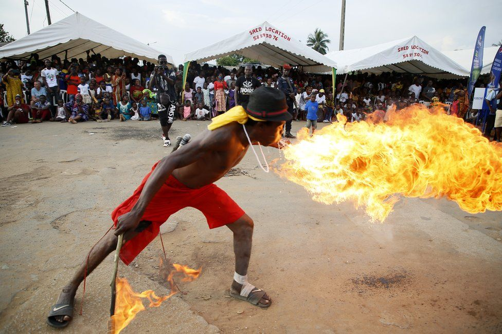 A man breathes fire as part of the parade, on the last day of the Popo Carnival in Bonoua, south of Abidjan.