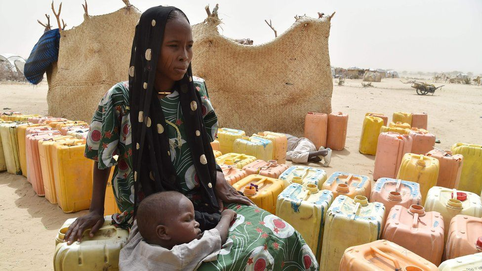 A displaced woman sits on a water can as she waits with her child to during a water distribute by agents from the UN System in a refugees camp of Kidjendi, around Diffa, southeastern Niger, on June 19, 2016.